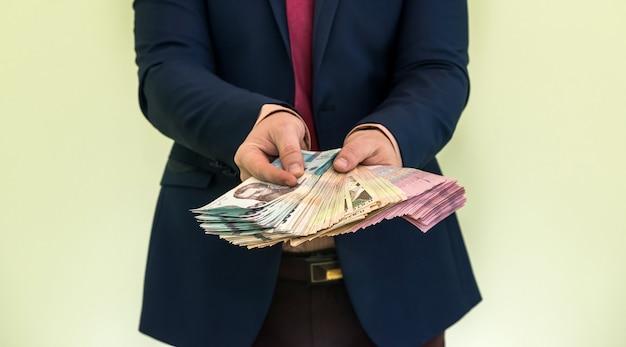 Un uomo in giacca e cravatta tiene una grossa pila di soldi ucraini e mostra il suo reddito