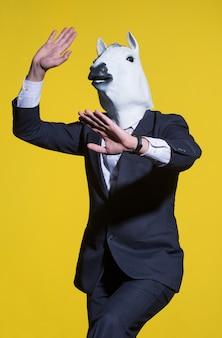 Un uomo con un vestito e una maschera da cavallo su uno sfondo giallo. sfondo aziendale concettuale