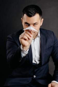 Un uomo in giacca e cravatta scuote un aeroplano di carta in mano. ritratto di affari. obiettivi stabiliti