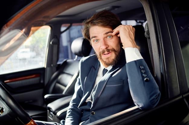 Uomo in tuta guardando fuori dal finestrino della macchina salam tuta finanza aziendale. foto di alta qualità