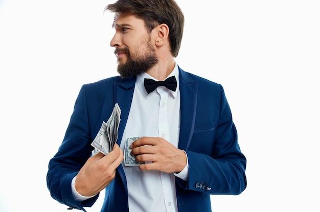Uomo in un vestito soldi in mano sfondo chiaro