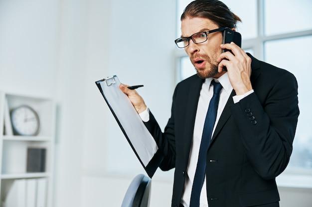 Uomo in un vestito vicino alle tecnologie del computer desktop dell'ufficio