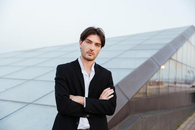Uomo vestito vicino a un edificio di vetro