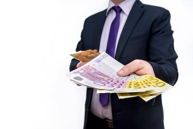 Uomo in abito che offre banconote in euro da vicino