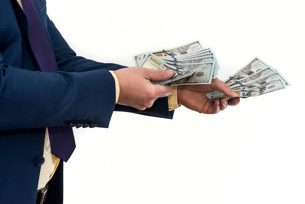 Un uomo in giacca e cravatta offre una tangente per un prodotto o servizio. l'uomo d'affari tiene e dà i dollari. corruzione o stipendio.