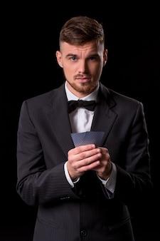 Uomo in abito in posa con carte per il gioco d'azzardo su sfondo nero