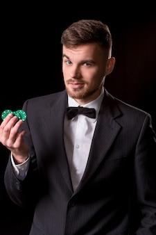 Uomo in abito in posa con fiches per il gioco d'azzardo su sfondo nero