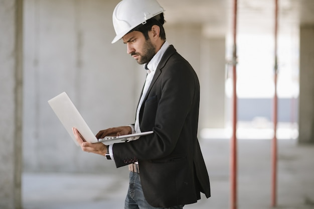 L'uomo in tuta e casco di sicurezza lavora sul computer portatile