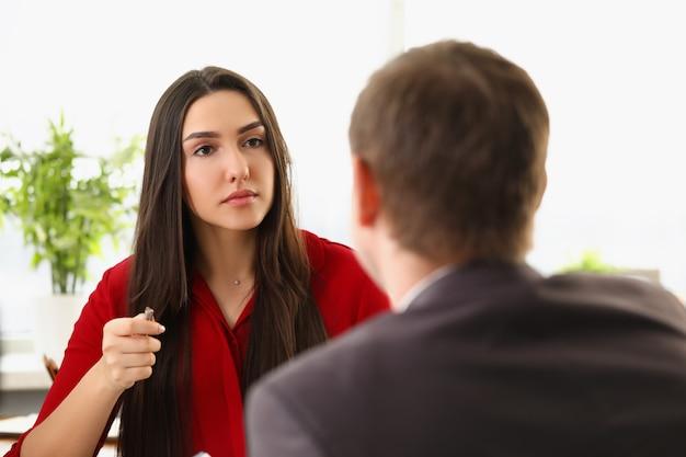 Un uomo in giacca e cravatta si siede in un ufficio e conduce un'intervista con una donna in abiti rossi giovane
