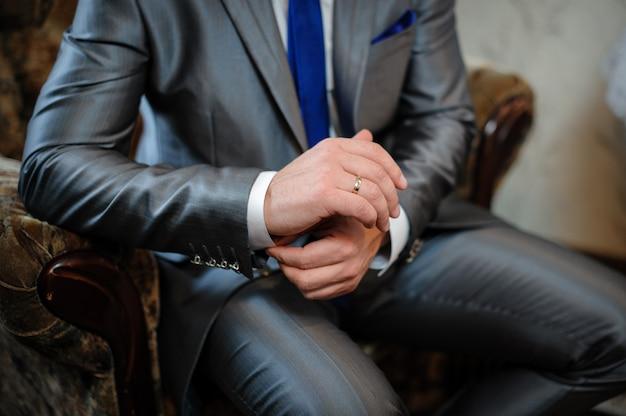 L'uomo in giacca e cravatta seduto su una sedia e mette gemelli