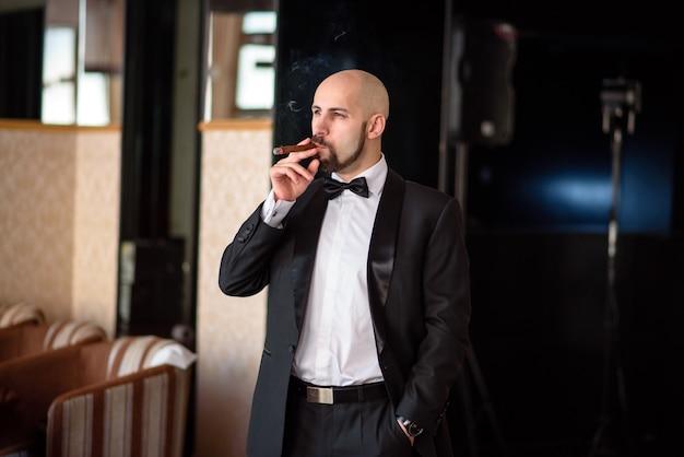 Un uomo in giacca e cravatta fuma un sigaro