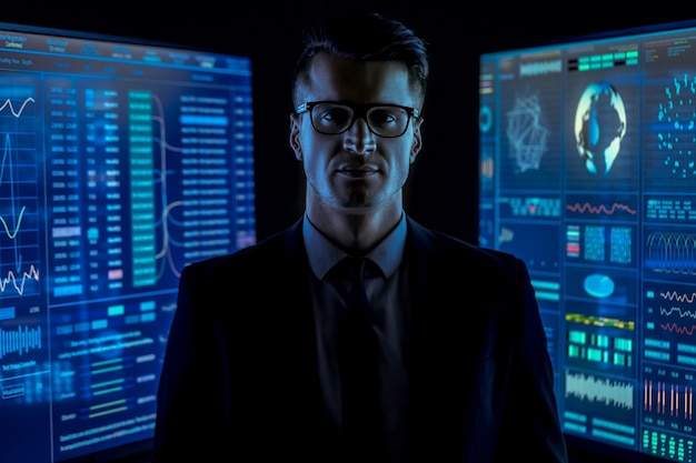 L'uomo vestito in piedi tra i monitor blu in una stanza buia