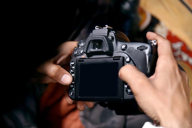Uomo in tuta che scatta foto. concetto di fotografia. il fotografo tiene in mano la fotocamera dsrl con sfondo sfocato bianco brillante all'interno in studio o in un negozio di matrimoni con messa a fuoco selettiva