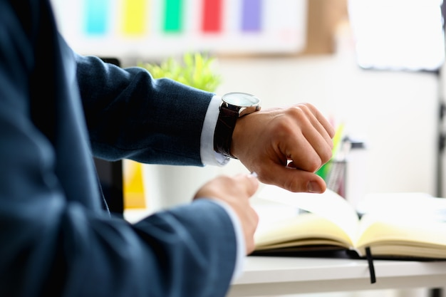 Uomo in giacca e cravatta check out time a orologio da polso argento