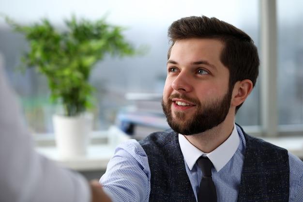 L'uomo in giacca e cravatta dà la mano come ciao in ufficio