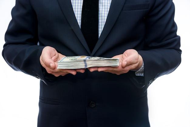 Uomo in tuta su sfondo bianco che mostra banconote in dollari