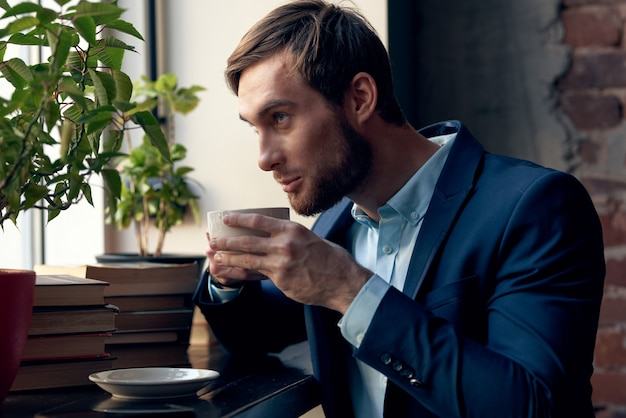 Uomo in un vestito con una tazza di caffè in mano colazione lifestyle per il tempo libero