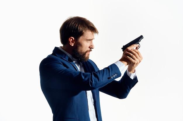 Uomo in abito con una pistola in mano sfondo chiaro