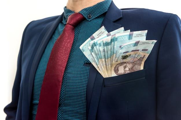 Un uomo vestito con un enorme mucchio di soldi ucraini