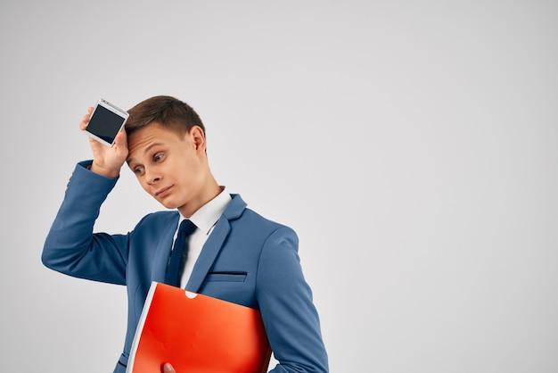 Un uomo vestito con una cartella rossa, un telefono in mano con tecnologia di comunicazione