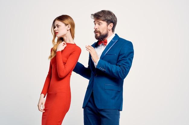 Un uomo in giacca e cravatta accanto a una donna con un vestito rosso che emoziona lo studio dei gesti delle mani