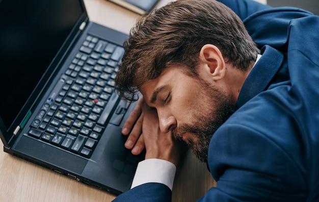 Uomo in un vestito a un tavolo di lavoro davanti a un ufficio portatile stanco