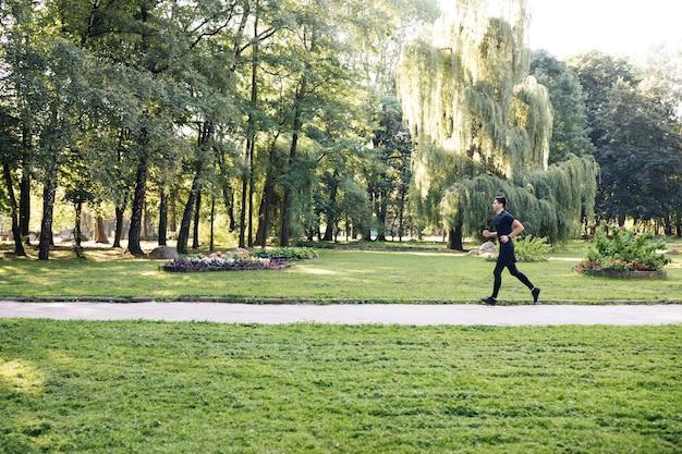 Uomo in divisa sportiva estiva in esecuzione nel parco cittadino con smartwatch per misurare la velocità