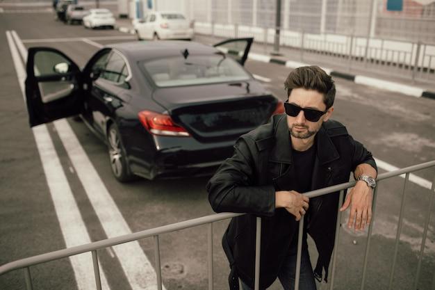 Un uomo in occhiali da sole e una giacca di pelle si trova vicino a un'auto sportiva