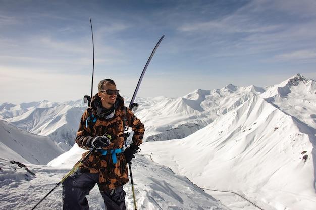 L'uomo in occhiali da sole posa con sci e altre attrezzature in cima alla montagna