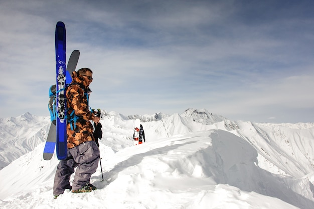 L'uomo in occhiali da sole con sci e altre attrezzature poggia sulla cima della montagna