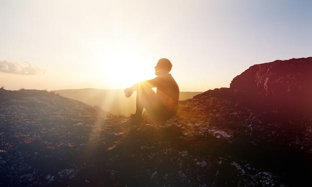Uomo alle montagne del tramonto