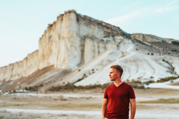 L'uomo nei raggi del tramonto su una roccia bianca