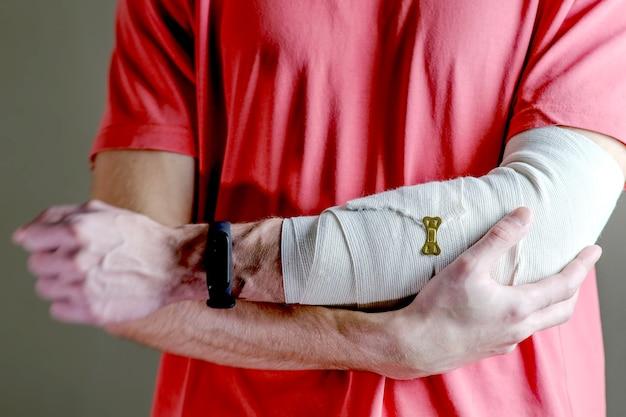 L'uomo sostiene la mano ferita. cure primarie la mano è fissata saldamente con un bendaggio elastico