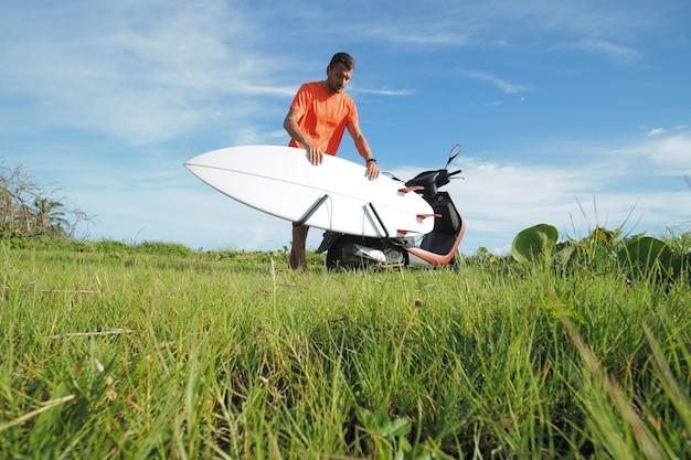 Il surfista dell'uomo che indossa la maglietta arancione prende la sua tavola da surf dal motorino dello scooter.