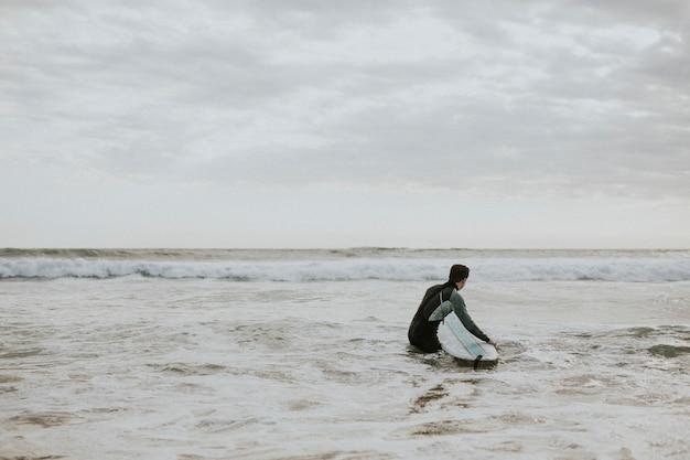 Uomo che fa surf in spiaggia