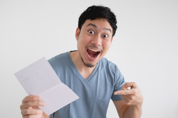 Uomo sorpresa e scioccato dalla lettera in mano sul muro isolato.