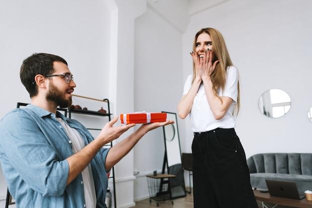 L'uomo ha sorpreso la sua ragazza con un regalo, coppia felice che celebra san valentino o anniversario