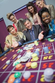 Uomo circondato da donne al tavolo della roulette