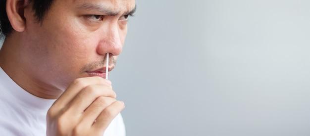 L'uomo esegue il test covid-19 con tampone per test rapido dell'antigene. coronavirus self nasale o home test, concetto di blocco e isolamento domestico