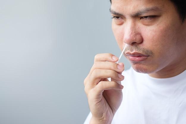 L'uomo esegue il test covid-19 con tampone per test rapido dell'antigene. coronavirus auto nasale o test a casa, concetto di blocco e isolamento domestico