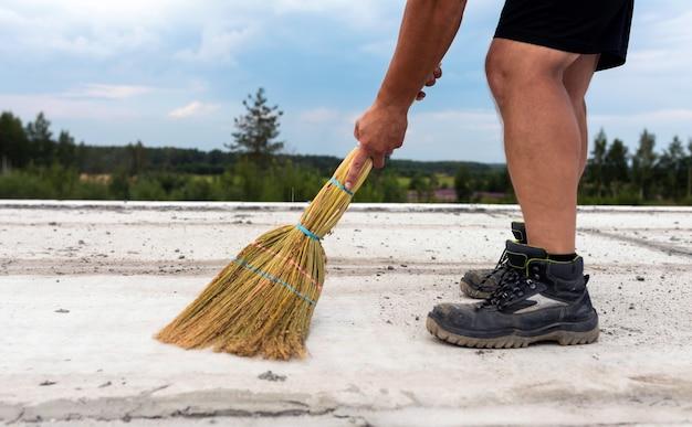 Un uomo spazza con una scopa il pavimento di cemento armato di un nuovo edificio