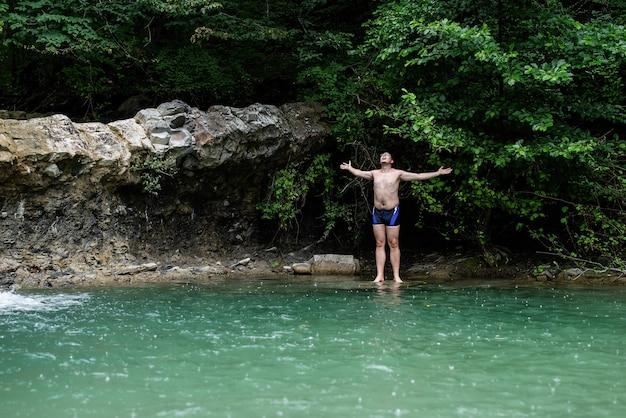 Uomo che nuota nel fiume di montagna con una cascata
