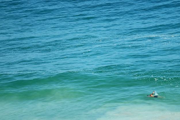 Uomo che nuota nell'oceano atlantico dai colori vivaci blu turchese