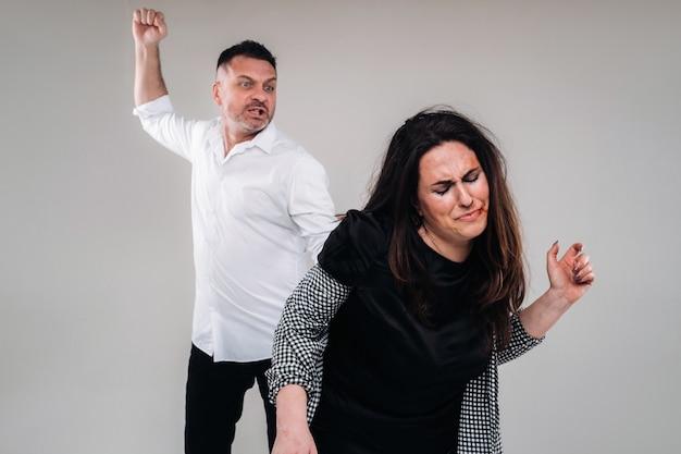 Un uomo agita il pugno contro una donna maltrattata in piedi su uno sfondo grigio. violenza domestica