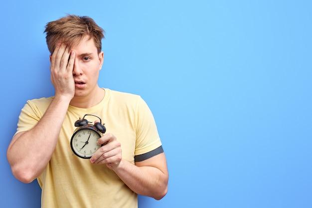 L'uomo in maglietta tiene la sveglia al mattino, non ha abbastanza sonno, non può svegliarsi. isolato su sfondo di colore blu ritratto in studio.