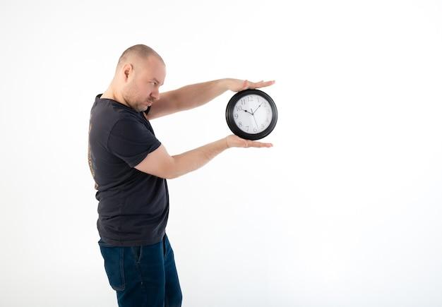Un uomo con una maglietta tiene in mano un grande orologio