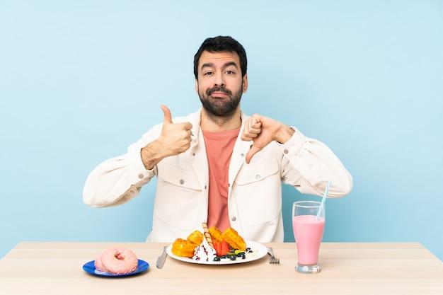 Uomo a un tavolo con cialde per la colazione e un frappè facendo segno buono-cattivo. indeciso tra sì o no