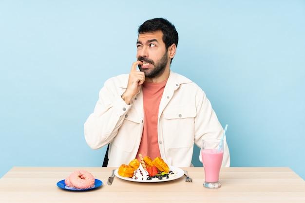Uomo a un tavolo con cialde per la colazione e un frappè nervoso e spaventato