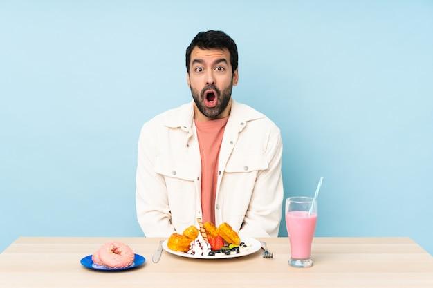Uomo a un tavolo con cialde per la colazione e un frappè con espressione facciale sorpresa