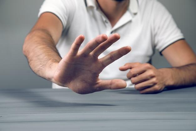 L'uomo al tavolo mostra no su un muro grigio con il palmo della mano